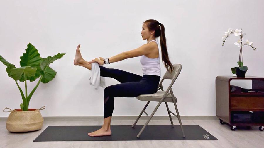 زنی بر روی صندلی نشسته و در حال ورزش است