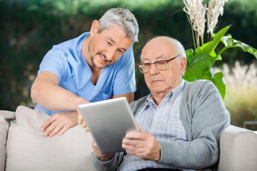 بیماری پارکینسونیسم - پیرمردی به همراه پرستار در حال کار با آیپد