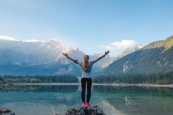 زنی ایستاده بر روی سنگ روبروی دریاچه